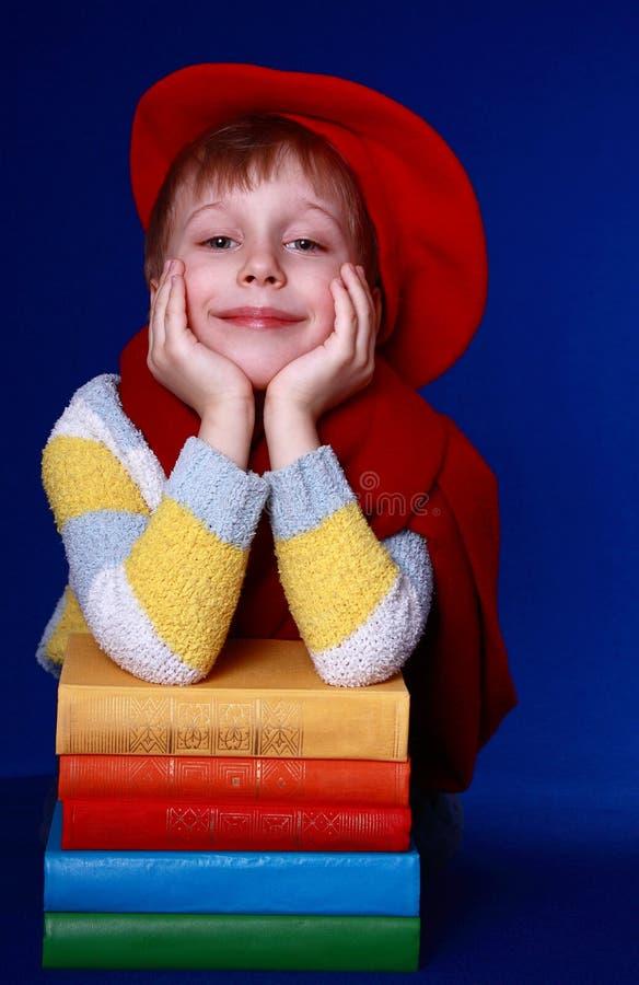 Ragazzo in berreto rosso con i libri variopinti   immagine stock