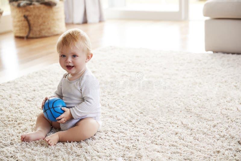 Ragazzo bianco del bambino che si siede sul pavimento nel salotto fotografie stock