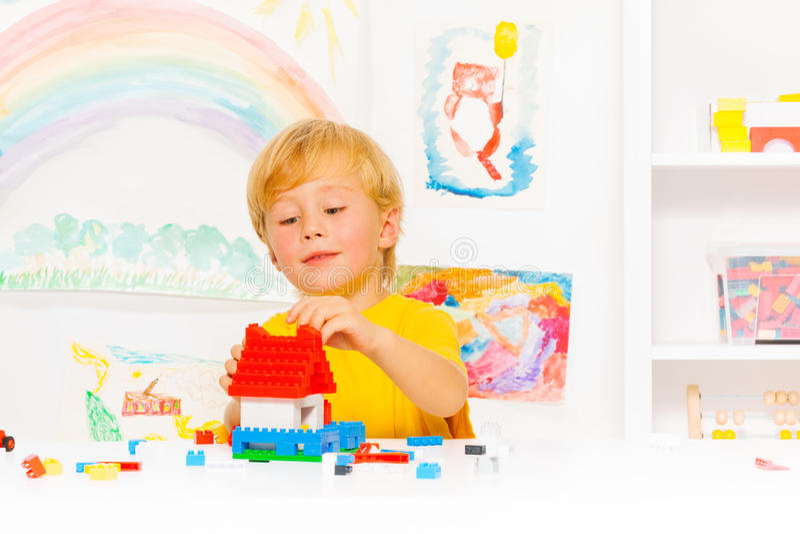 Ragazzo biondo bello che gioca con i blocchi di plastica immagini stock