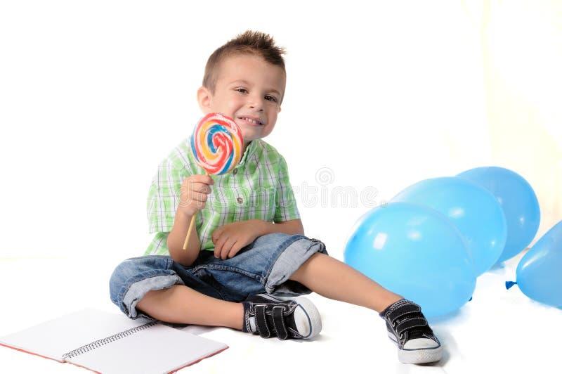 Ragazzo biondo con la lecca-lecca nella sua bocca fotografie stock