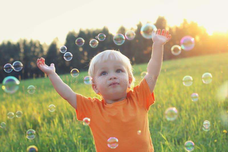 Ragazzo biondo del bambino sveglio che gioca con le bolle di sapone sul campo di estate Concetto felice di estate del bambino Imm immagini stock libere da diritti