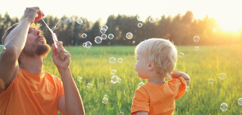 Ragazzo biondo del bambino sveglio che gioca con le bolle di sapone sul campo di estate Concetto felice di estate del bambino Imm immagine stock libera da diritti