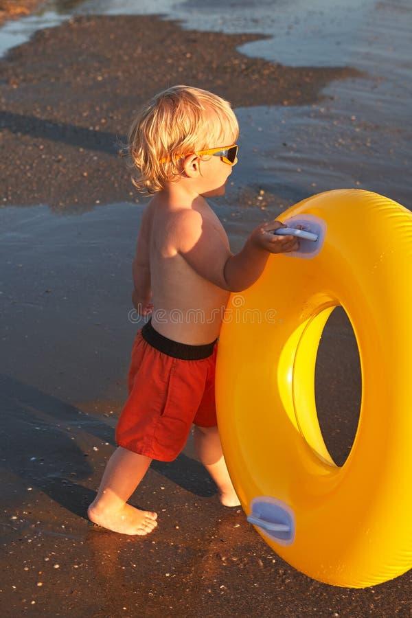 Ragazzo biondo in occhiali da sole con l'anello gonfiabile sulla spiaggia del mare fotografia stock libera da diritti