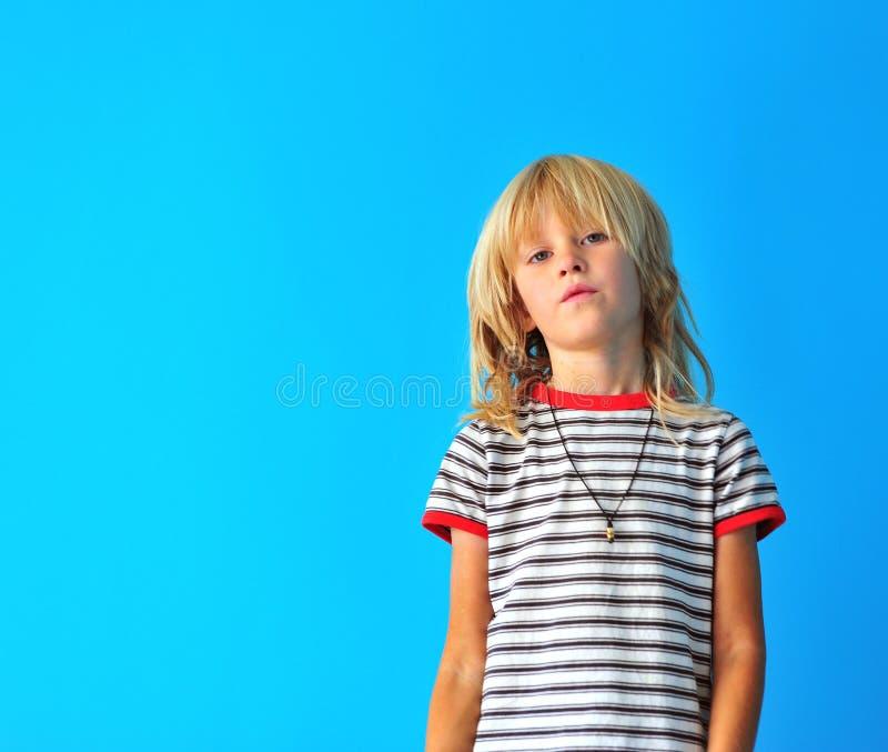 Ragazzo biondo sveglio alla parete blu fotografia stock