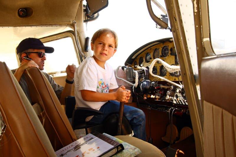 Ragazzo in cabina di guida dell'aeroplano privato immagine stock