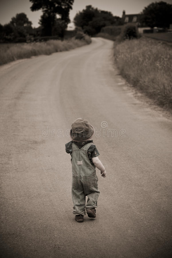 Ragazzo in cappello che cammina giù la strada immagine stock