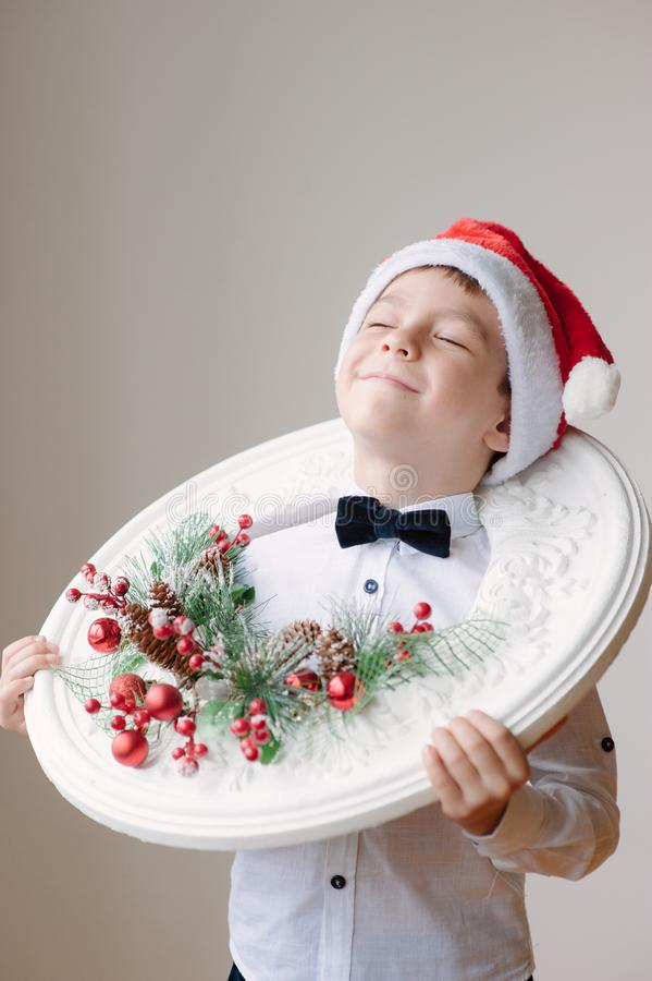 Ragazzo in cappello di Santa con le decorazioni di Natale fotografia stock