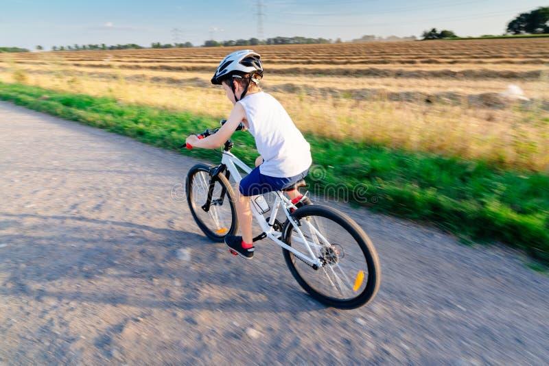 Ragazzo in casco bianco che guida la sua bicicletta immagine stock libera da diritti
