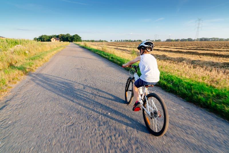 Ragazzo in casco bianco che guida la sua bicicletta fotografia stock