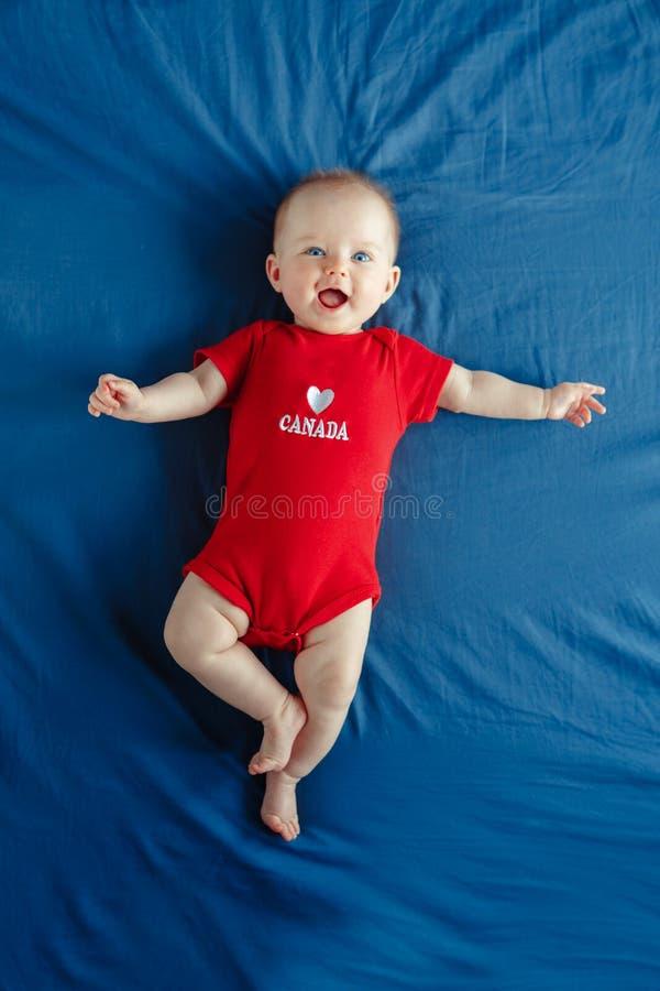 Ragazzo caucasico bianco sorridente adorabile sveglio della neonata con gli occhi azzurri quattro mesi fotografia stock