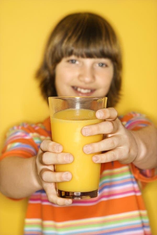 Ragazzo caucasico con vetro del succo di arancia. fotografia stock libera da diritti
