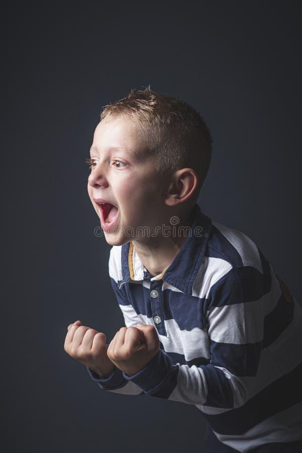 Ragazzo caucasico del bambino di 6 anni che grida nella disperazione immagini stock