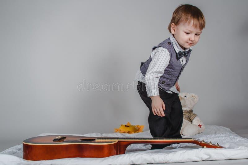 Ragazzo caucasico di due anni in cravatta a farfalla e maglia con la chitarra acustica su fondo grigio fotografia stock