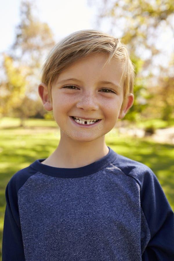 Ragazzo caucasico di sette anni in un parco, ritratto verticale fotografie stock libere da diritti