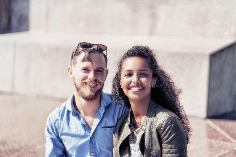 Ragazzo caucasico sorridente insieme Lituania felice della giovane ragazza del Medio-Oriente fotografia stock libera da diritti