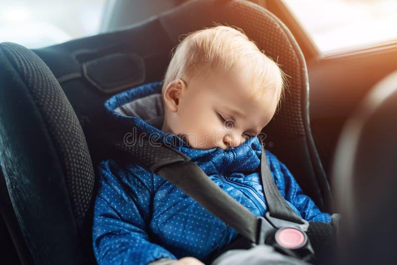 Ragazzo caucasico sveglio del bambino che dorme nel sedile di sicurezza del bambino in automobile durante il viaggio stradale Sog immagine stock libera da diritti