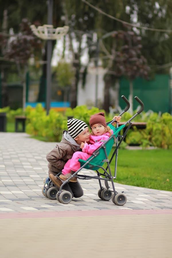 Ragazzo che abbraccia neonata che si siede in un passeggiatore Fratello e sorella su una passeggiata nel parco, giorno adorabile  fotografia stock