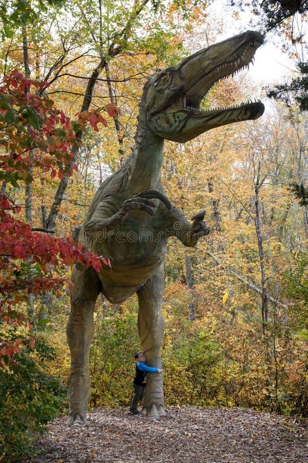 Ragazzo che abbraccia un dinosauro a grandezza naturale fotografia stock libera da diritti