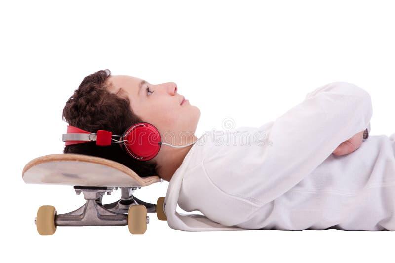 Ragazzo che ascolta la musica con la sua testa sul pattino immagini stock libere da diritti