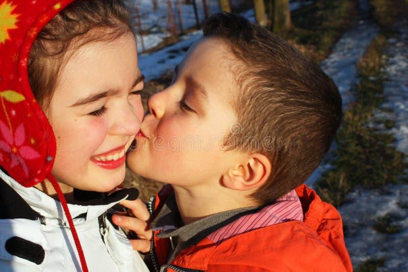 Ragazzo che bacia una ragazza, cuori intorno immagini stock