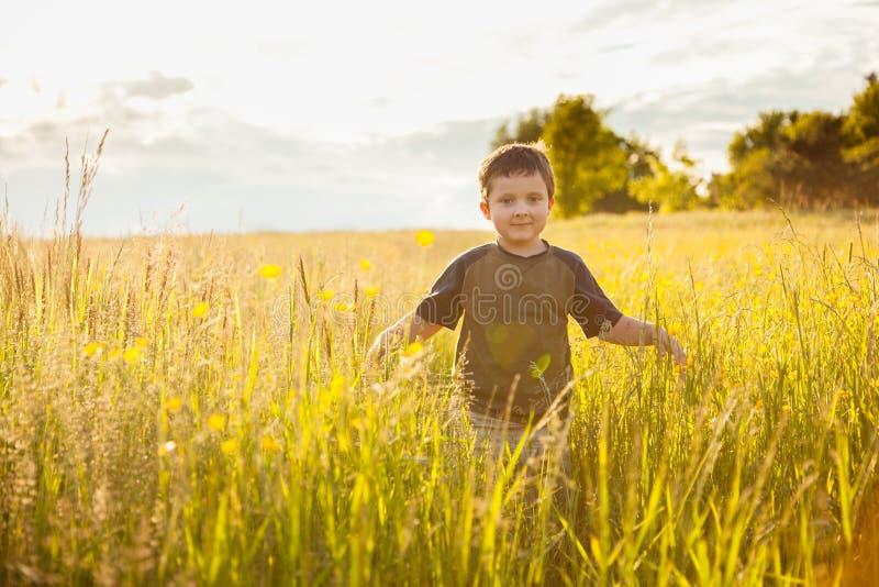 Ragazzo che cammina in un campo fotografia stock