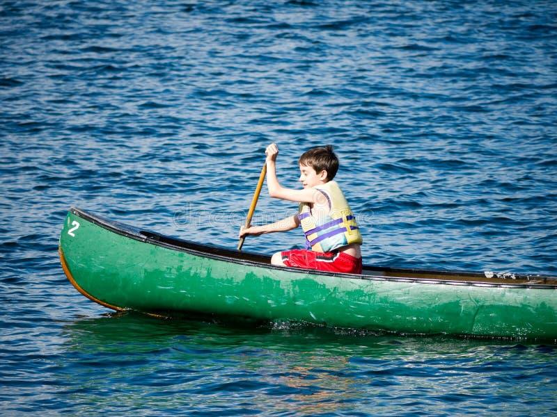 Ragazzo che Canoeing al campeggio estivo fotografia stock