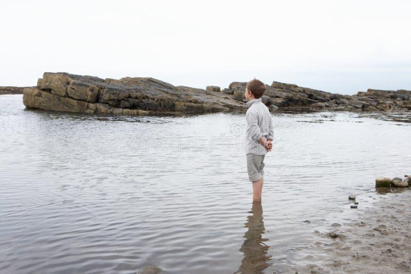 Ragazzo che daydreaming sulla spiaggia fotografia stock