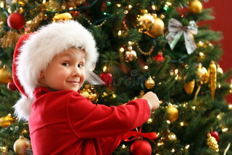 Ragazzo che decora l'albero di Natale fotografie stock