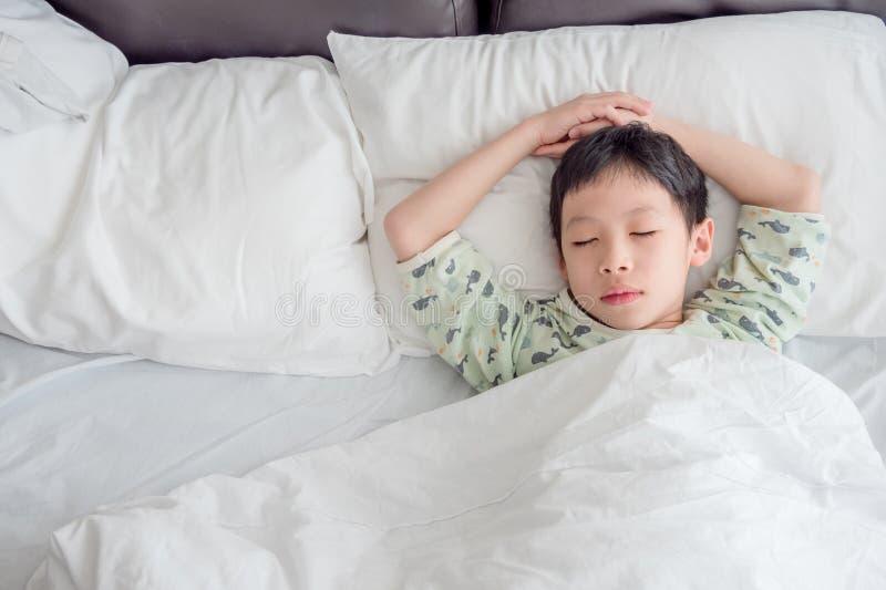 Ragazzo che dorme sul letto nella mattina immagini stock