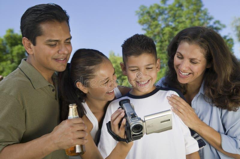 Ragazzo (13-15) che esamina videocamera portatile con la famiglia all'aperto. immagini stock