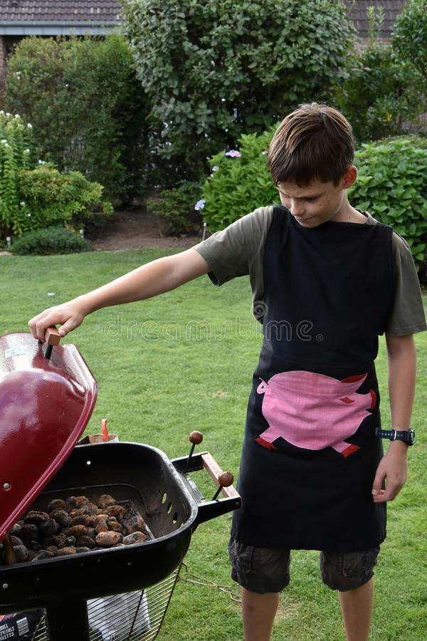 Ragazzo che fa barbecue fotografie stock libere da diritti