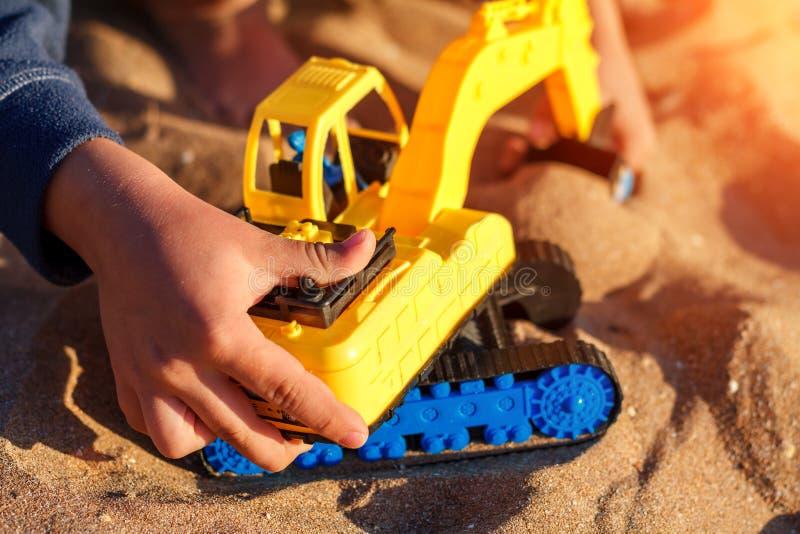 Ragazzo che gioca con il giocattolo nella sabbia fotografie stock libere da diritti