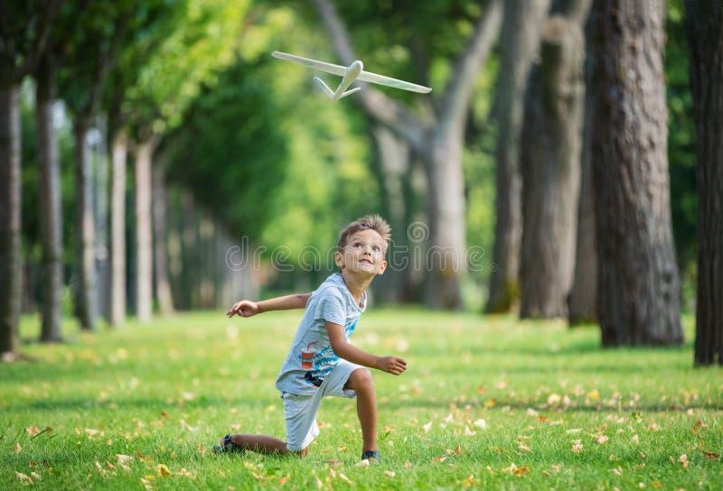 Ragazzo che gioca con l'aliante del giocattolo in parco fotografie stock libere da diritti