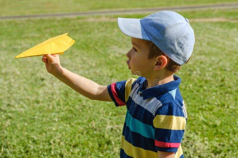 Ragazzo che gioca con un aereo giallo del giocattolo al parco un giorno soleggiato immagini stock libere da diritti