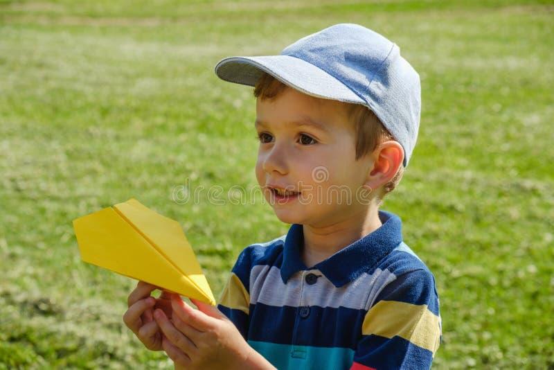 Ragazzo che gioca con un aereo giallo del giocattolo al parco un giorno soleggiato fotografie stock