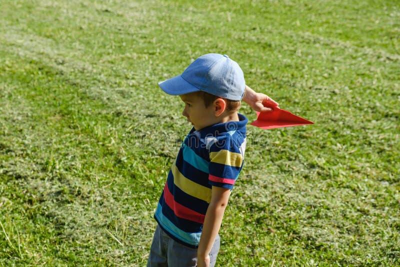 Ragazzo che gioca con un aereo rosso del giocattolo al parco un giorno soleggiato fotografia stock libera da diritti