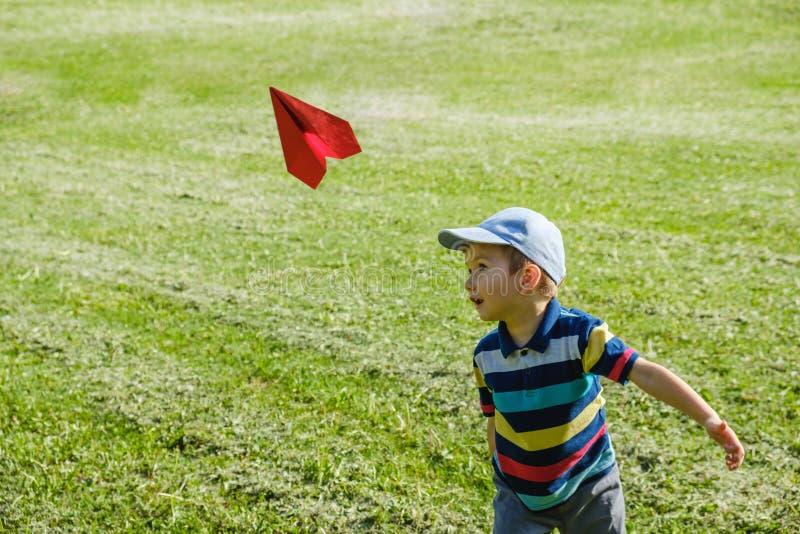 Ragazzo che gioca con un aereo rosso del giocattolo al parco un giorno soleggiato immagine stock