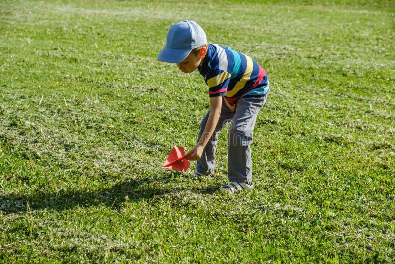 Ragazzo che gioca con un aereo rosso del giocattolo al parco un giorno soleggiato immagine stock libera da diritti