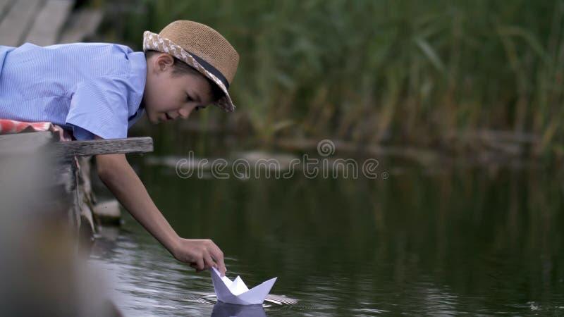 Ragazzo che gioca con una barca di carta nel lago sul pilastro immagine stock libera da diritti