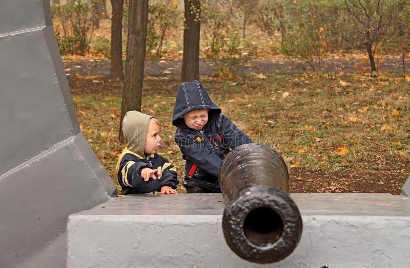 Ragazzo che gioca con una pistola del giocattolo sulla via in autunno immagine stock