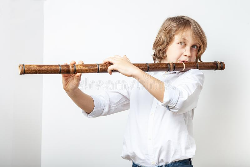Ragazzo che gioca flauto di bambù fotografie stock libere da diritti