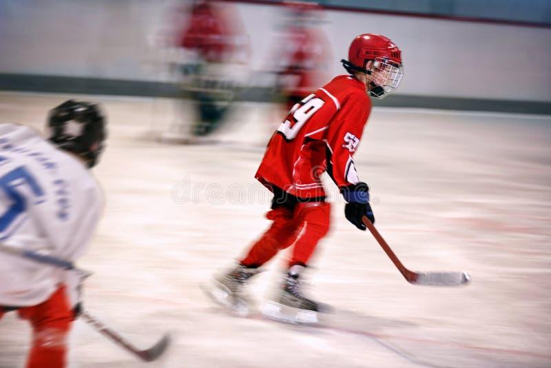 Ragazzo che gioca hockey su ghiaccio sulla pista di pattinaggio immagine stock