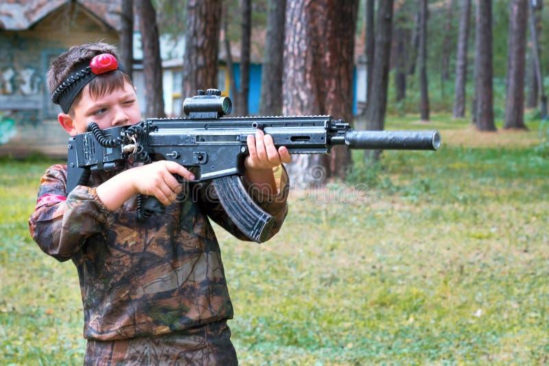 Ragazzo che gioca il ce l'hai del laser all'aperto Gioco tattico militare fotografia stock