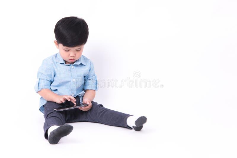 Ragazzo che gioca telefono cellulare su fondo bianco immagini stock