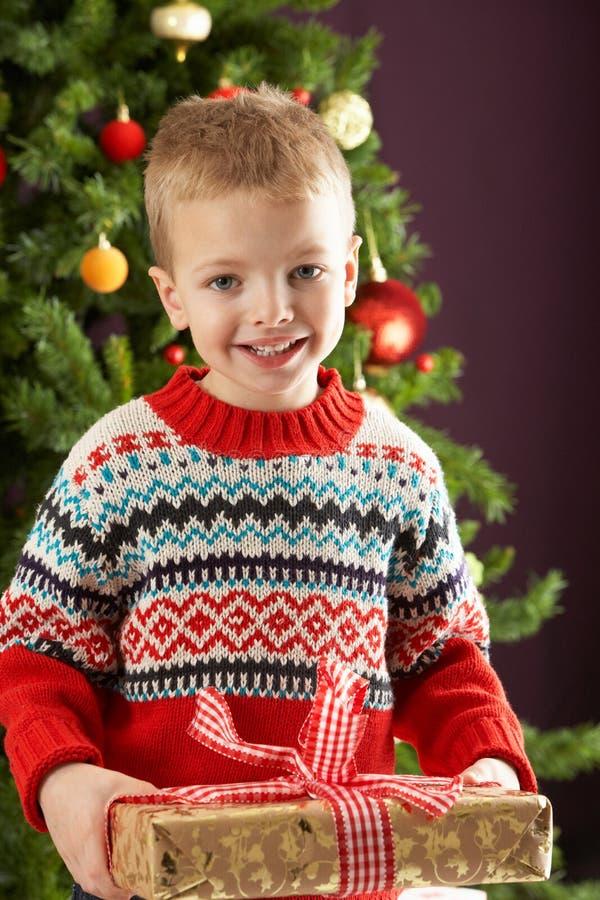Ragazzo che giudica presente davanti all'albero di Natale fotografia stock