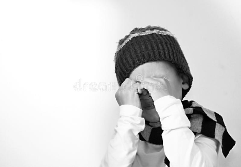 Ragazzo che grida nella povertà con gli strappi in sua foto di riserva degli occhi immagini stock libere da diritti