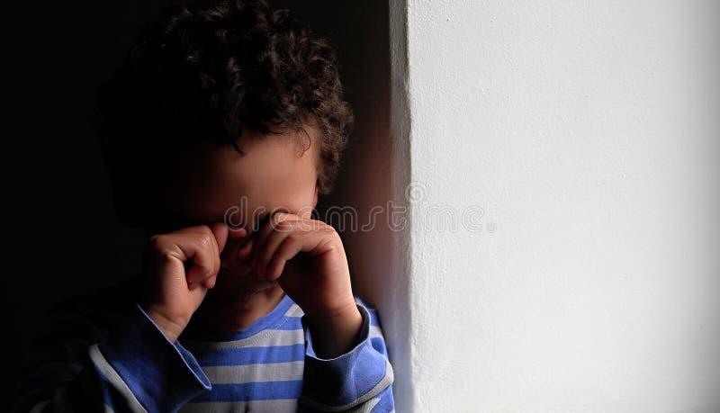 Ragazzo che grida nella povertà con gli strappi in sua foto di riserva degli occhi fotografie stock