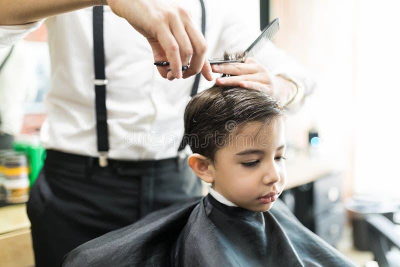 Ragazzo che ha taglio di capelli con il pettine e forbici a Barber Shop immagini stock libere da diritti
