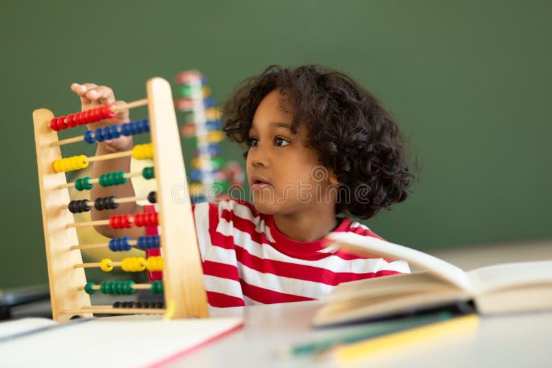 Ragazzo che impara matematica con l'abaco in un'aula fotografia stock libera da diritti