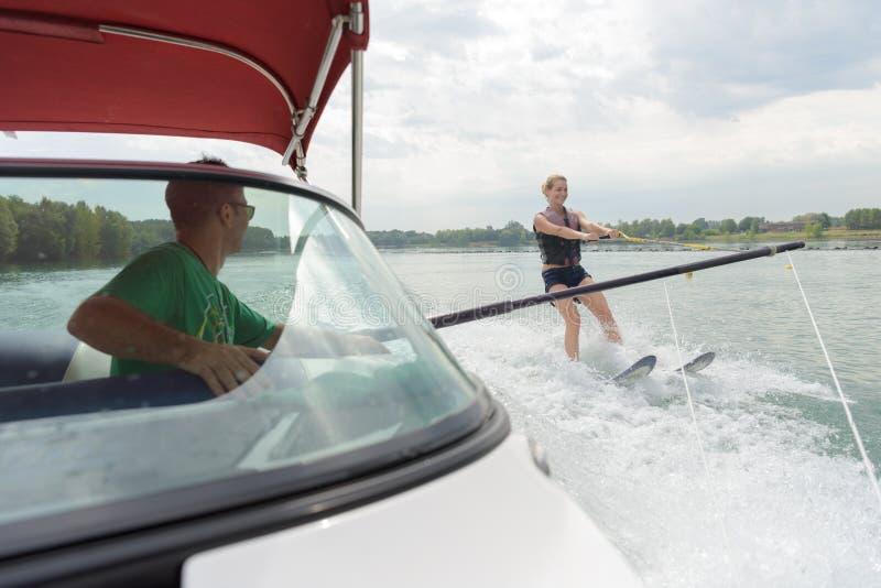 Ragazzo che impara sci d'acqua con l'istruttore sulla barca fotografie stock libere da diritti